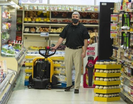 Lift-Rite Edge pallet truck being used in grocery store to restock shelves.